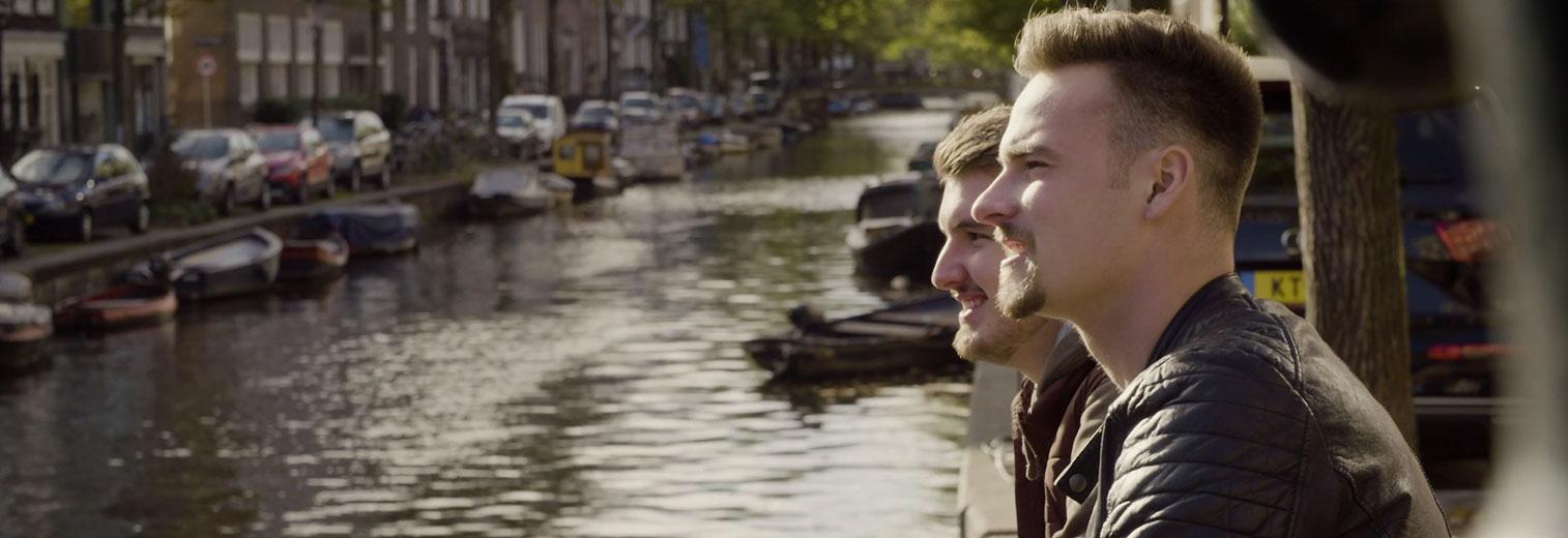 Leon und Leon sitzen während des Auslandspraktikums an einer Gracht in Amsterdam.