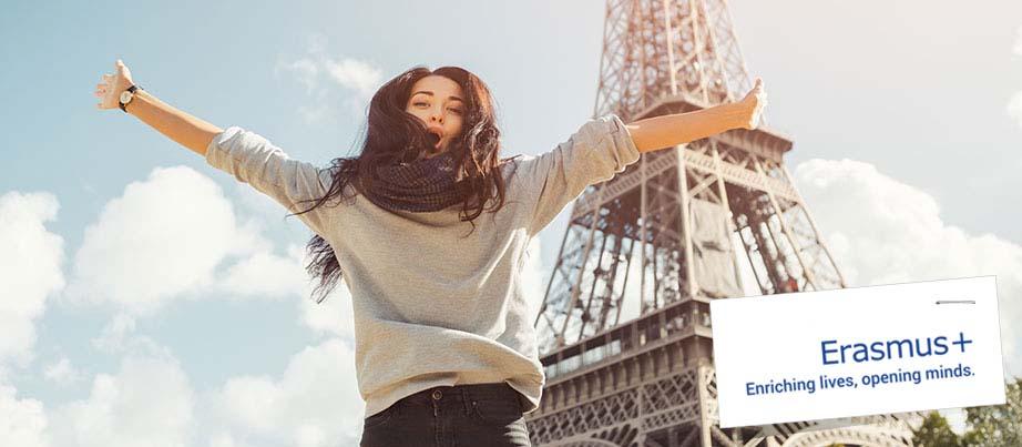 Eine junge Frau vor dem Eifelturm in Paris.