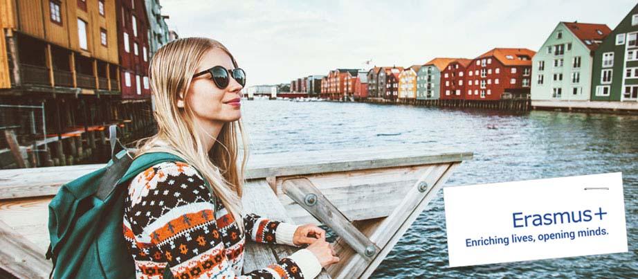 Eine junge Frau im Auslandspraktikum steht an einem Fluss in einer norwegischen Stadt.