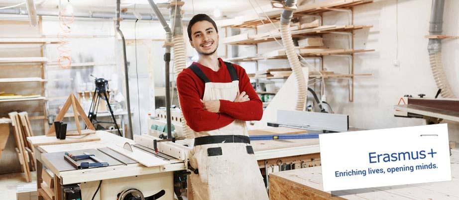 Ein Auszubildender steht in einer Schreinerwerkstatt.