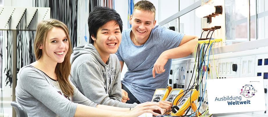 Drei Auszubildende der Elektrotechnik am Werktisch