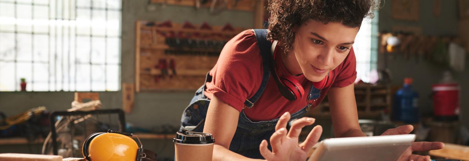 Junge Frau in der Schreinerei sucht freudig etwas auf einem Tablet