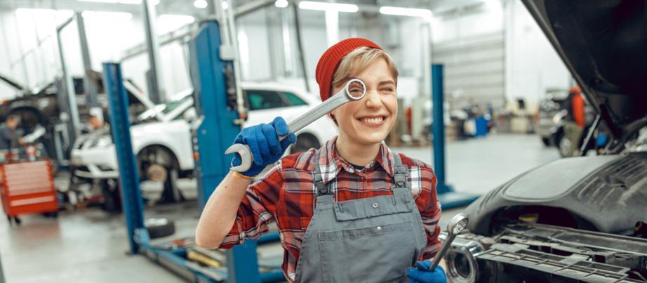 Eine Auszubildende in der Autowerkstatt hält gut gelaunt einen Schraubschlüssel vors Auge.