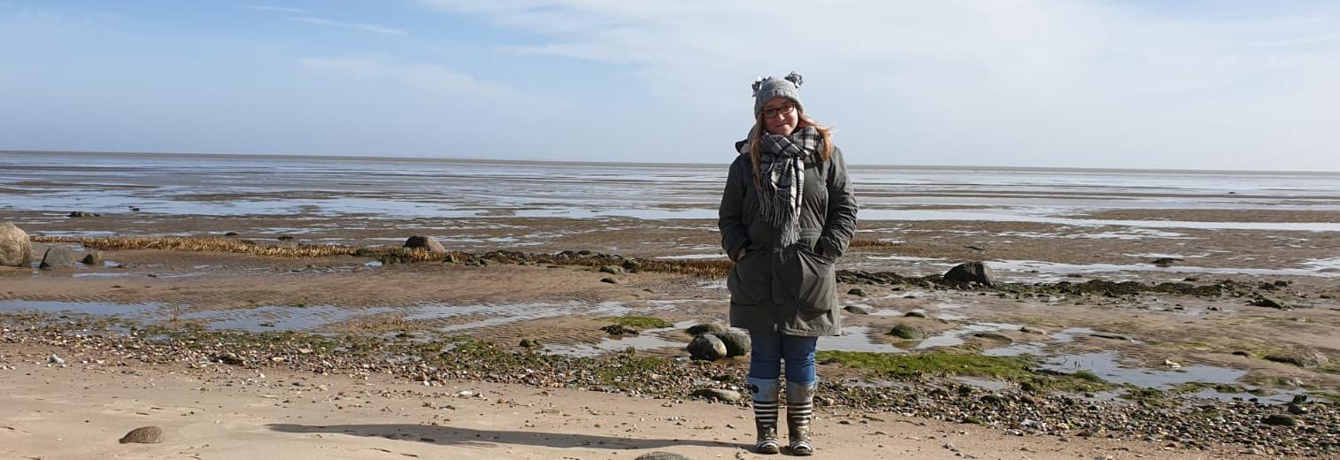 Franziska in warmer Kleidung am Strand von Dänemark.