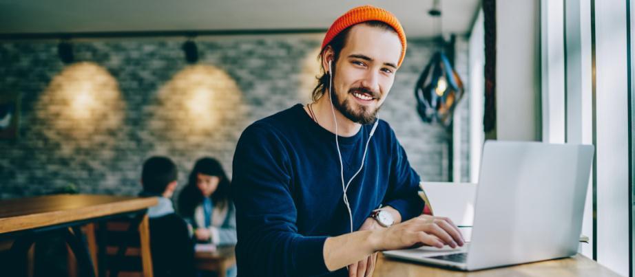 Ein junger Auszubildender arbeitet im Café am PC.