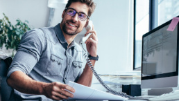 Fröhlicher Mann am Büroarbeitsplatz telefoniert.